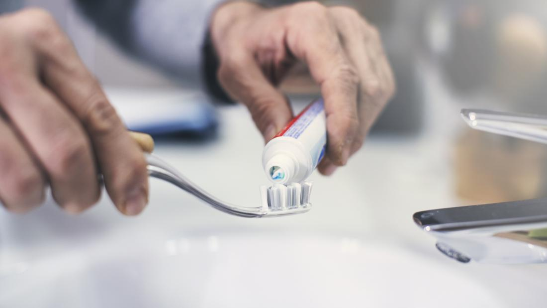 man putting toothpaste on a tooth brush
