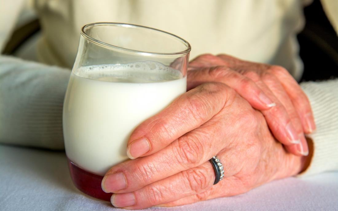 a woman holding a glass of dairy milk that may give her acid reflux