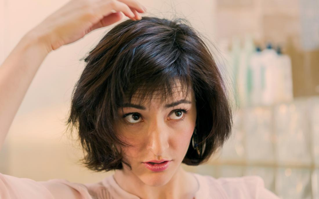 a woman checking her head for hair loss from seborrheic dermatitis