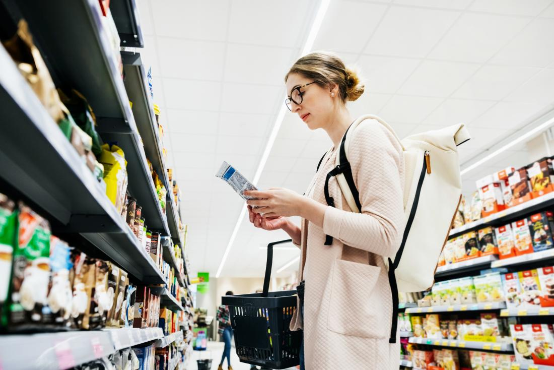 Woman reading label in supermarket
