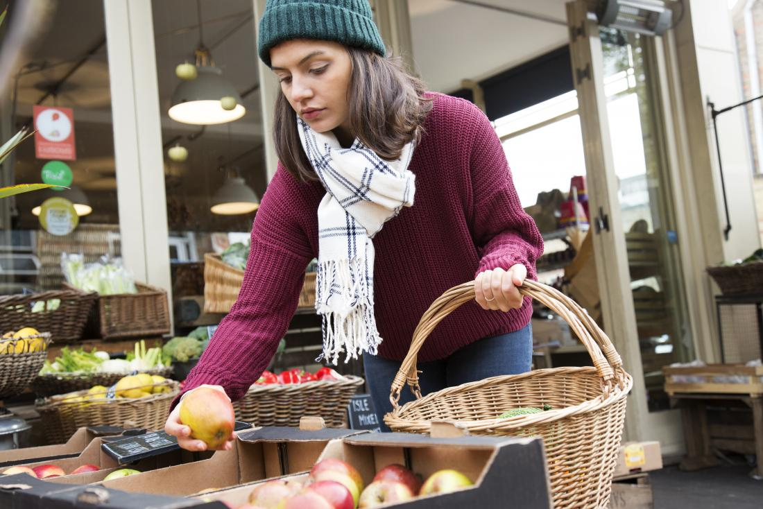 a woman reducing food waste by only buying the apples she plans to eat.