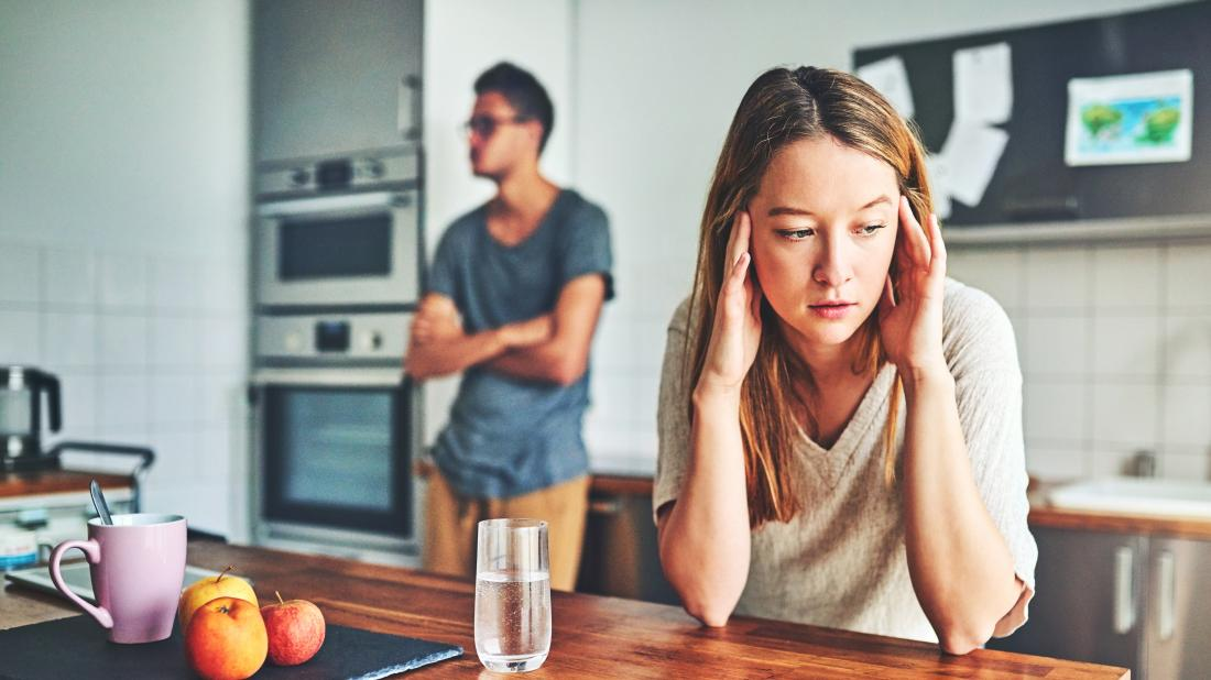 a woman looking sad in her kitchen as she is experiencing verbal abuse.