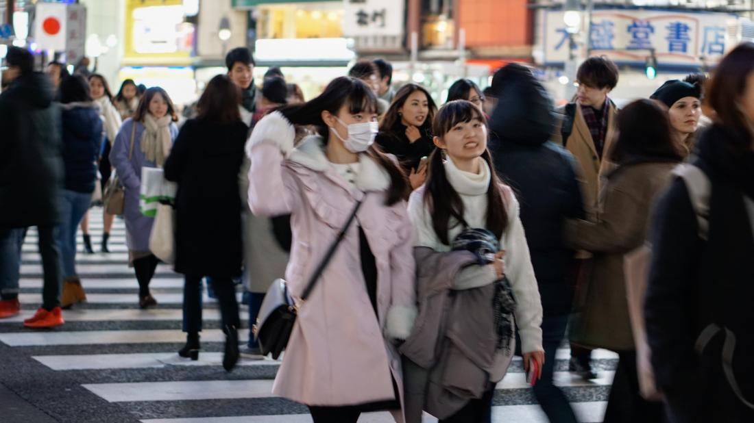 young woman wearing face mask on the street
