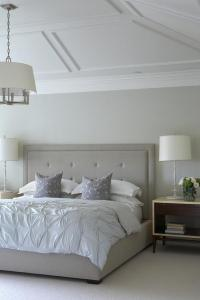 Gray Tufted Bed Under Vaulted Ceiling with Decorative Trim ...