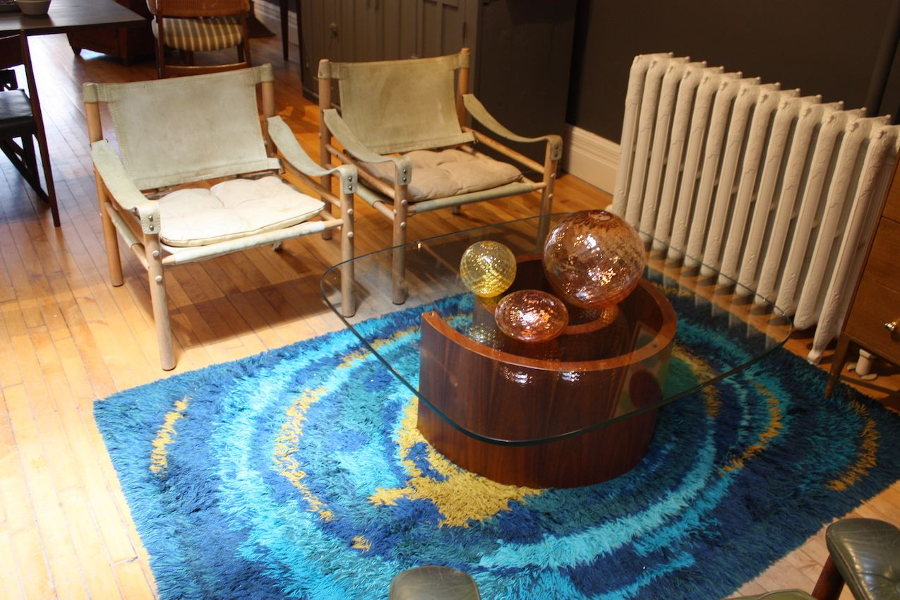 We love this grouping not just for the bold pop of color from the rug. The unexpected combination of vintage safari campaign chairs with a glass topped swirl of a modern table is simply delightful
