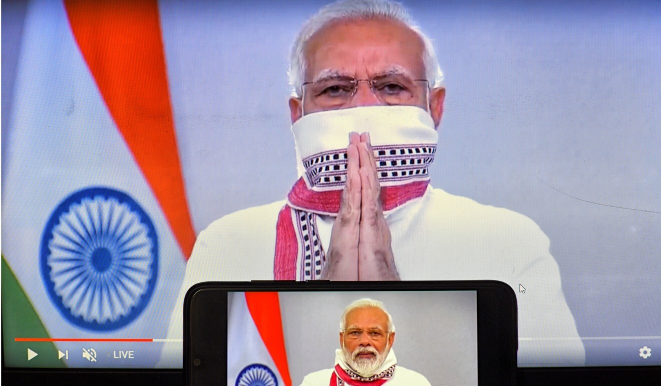 Indian Prime Minister Narendra Modi is seen on a smartphone and a screen during one of his televised addresses. Photo: DPA