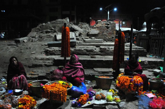 Women sell flowers at dusk in front of archaeological monuments damaged by the April 2015 earthquake in Durbar Square Kathmandu. Credit: Amantha Perera/IPS