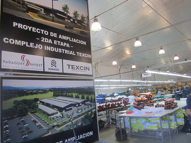 Texcin's textile warehouse seen behind a sign announcing the expansion of the plant which was built by Brazilian company Riachuelo with partners in Paraguay on the outskirts of Asunción. Credit: Mario Osava/IPS