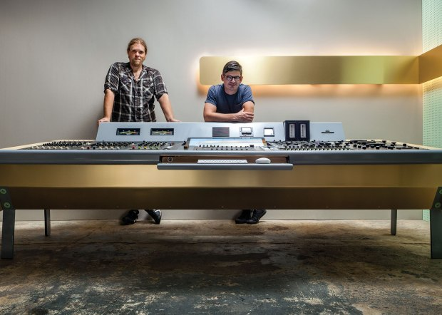 author standing behind large table-sized audio console of knobs and switches