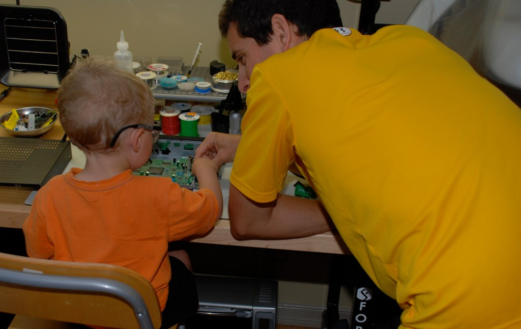 Joe and his son taking apart a satellite TV receiver