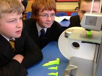 School children watch the Cube 3D printer at work.