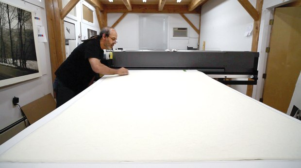 The thick handmade paper is affixed to a carrier sheet. Any lint or stray fibers are carefully removed prior to printing. This sheet costs about $500.