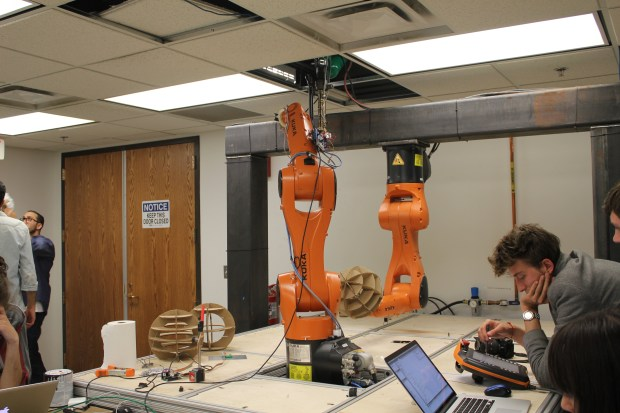 Robot manipulates a form that another robot controlled extruder will deposit plastic onto.