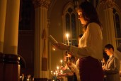Visitors hold up their candle during the Paschal Vigil Mass.
