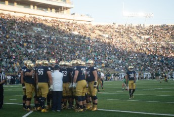 Coach Harry Hiestand has a last minute huddle with the starting offensive line.