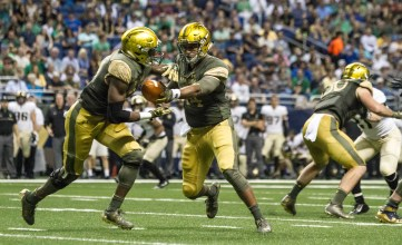 DeShone Kizer hands the ball to an Irish running back.