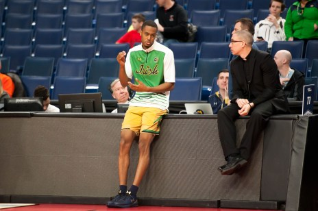 Irish senior forward V.J. Beachem and Fr. Pete McCormick chat before their game against Princeton.