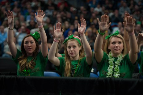 Members of the Irish Band raise their hands in support of an Irish free throw attempt.