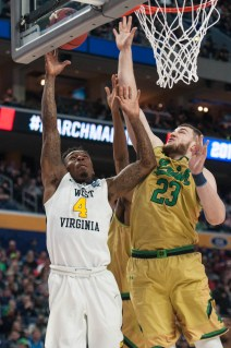 Irish junior forward Martinas Geben blocks a West Virginia player's shot during Notre Dame's 83-71 loss to the Mountaineers on Saturday at KeyBank Arena.
