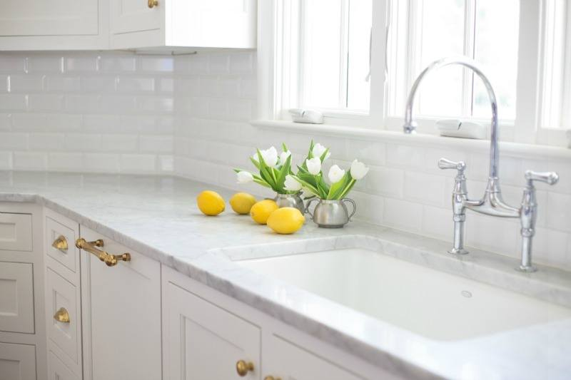 Designer Jenna Wallis loves a clean, uncluttered kitchen countertop. Beveled white subway tile extends to the Carrara marble countertop, and outlets are tucked away under cabinetry for a clean aesthetic.