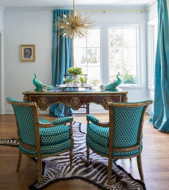 The study features pale, lacquered walls and peacock blue accents. A starburst fixture highlights Jenna's love of whimsy.