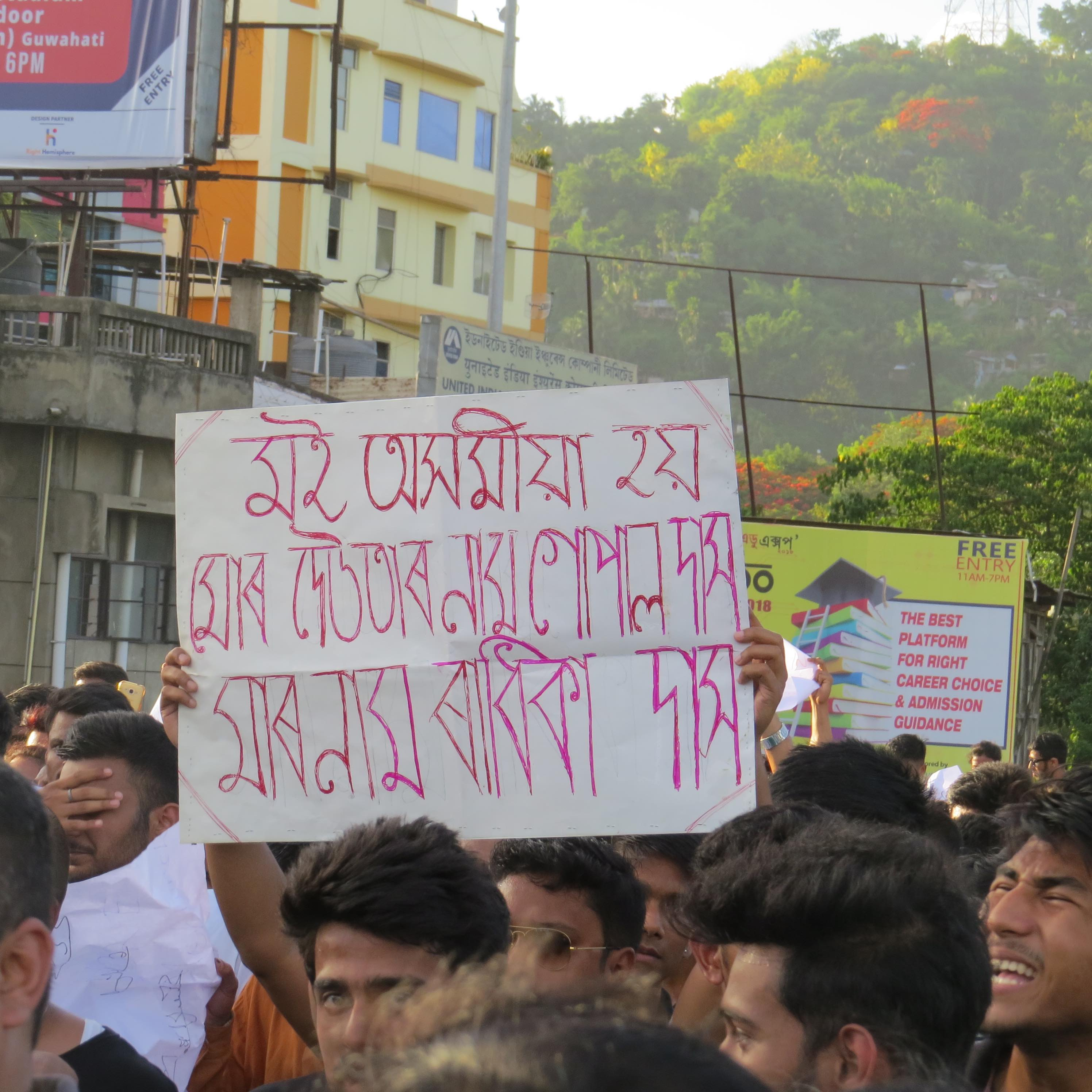 """At a spontaneous protest in Guwahati on June 10, a protestor holds up a poster that quotes Nilotpal Das's last words that were captured on video. He said, """"'I am an Assamese. My father's name is Gopal Das. My mother's name is Radhika Das."""" Credit: Shaheen Ahmed"""