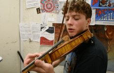 Stony Brook student Samuel Vodopia is playing violin in a practice room.