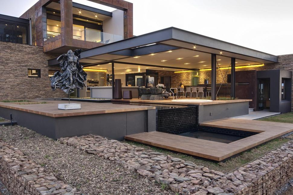 Geometric Concrete And Steel Home With Stone And Water Elements