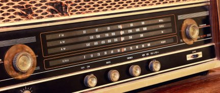 This is a close-up of vintage radio buttons and a tuner control panel (Shutterstock/MBR9292)