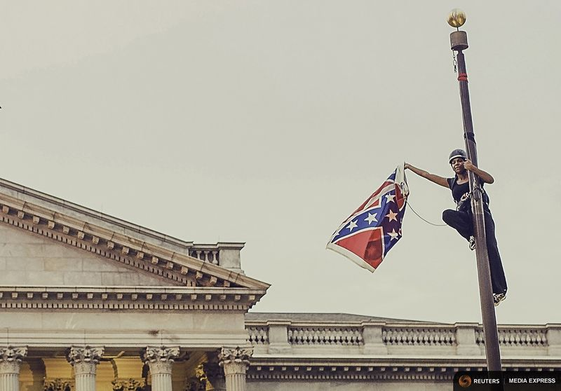 (Bree Newsome takes down the flag. Reuters Media Express/Adam Anderson Photos)