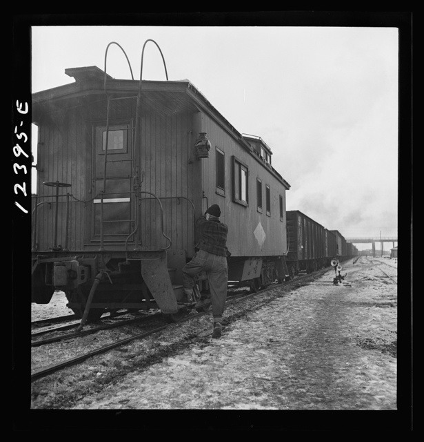 Chicago, Illinois Freight conductor boarding the caboose of a train