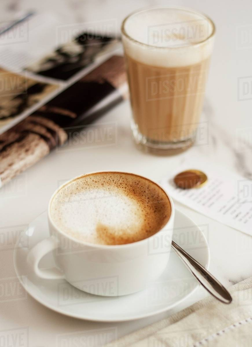 Caffe Latte A Cappucino And A Caffe Latte Next To A Magazine Stock Photo