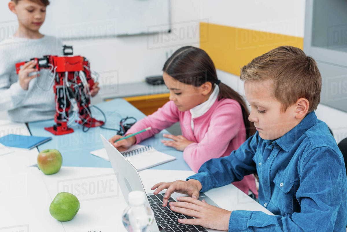 Children Robot Children Writing In Notebooks Typing Laptop And Touching Red Robot In Stem Class Stock Photo