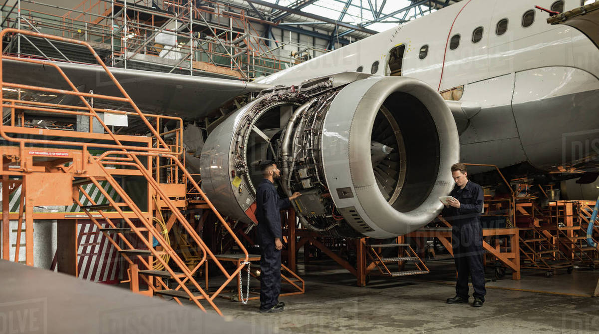 Airplane Maintenance Aircraft Maintenance Engineers Examining Turbine Engine Of Aircraft At Airlines Maintenance Facility Stock Photo