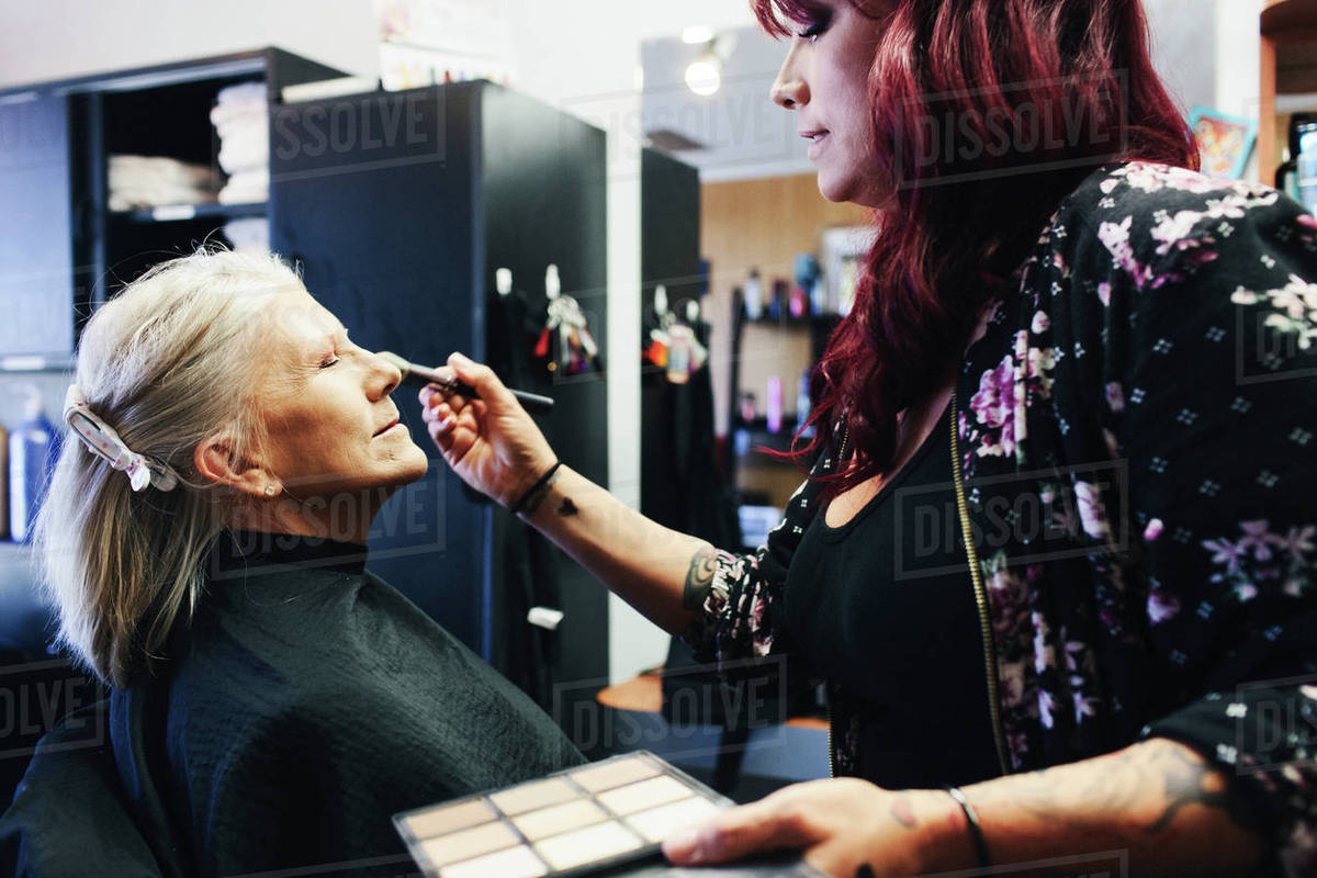 Salon Senior Beautician Applying Make Up On Senior Woman At Salon Stock Photo