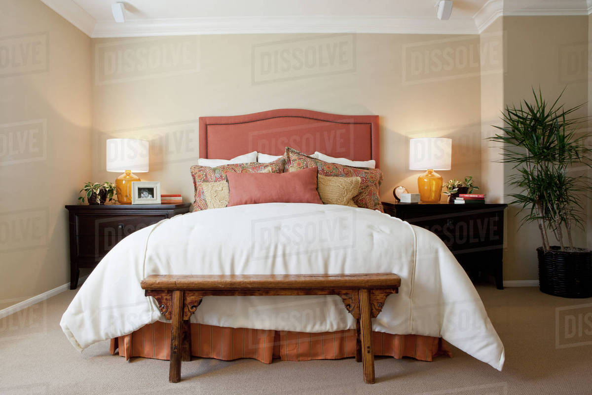 Bed Table Lamps Arranged Pillows On Tidy Bed With Lit Table Lamps In The Bedroom At Home Stock Photo