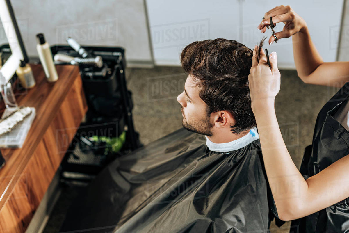 Salon Angle High Angle View Of Hairdresser Cutting Hair To Handsome Young Man In Beauty Salon Stock Photo