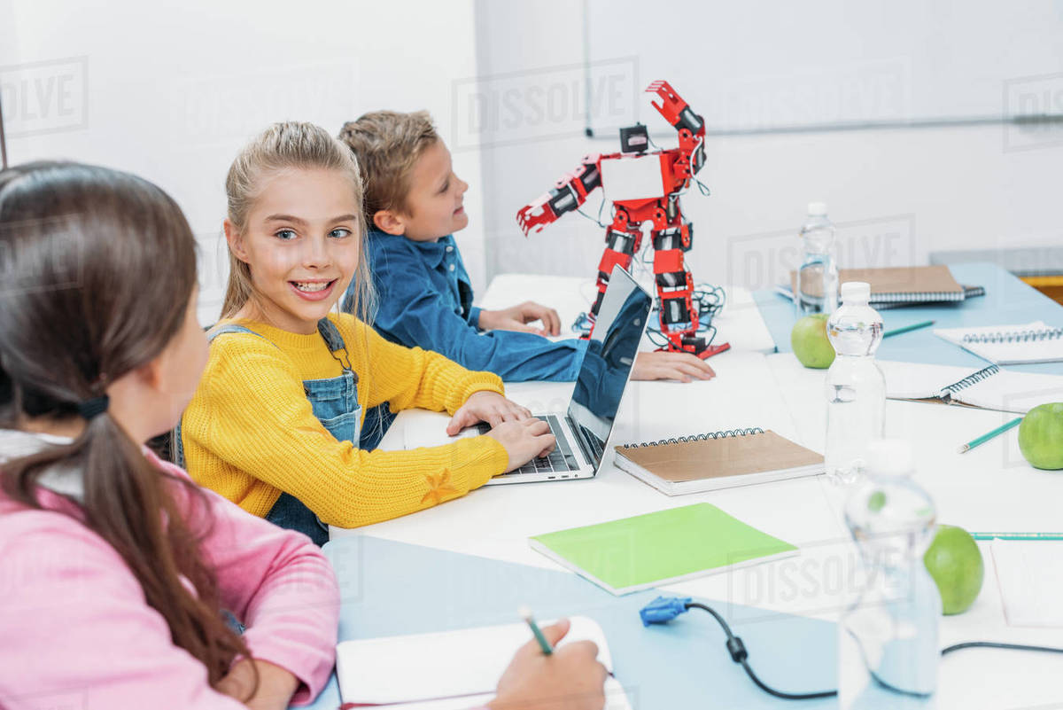 Children Robot Children Writing In Notebook And Using Laptop At Desk With Red Robot In Stem Class Stock Photo