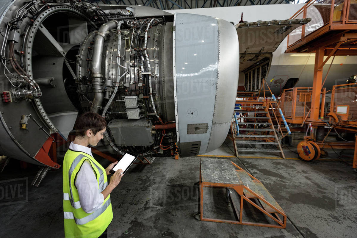 Airplane Maintenance Female Aircraft Maintenance Engineer Examining Turbine Engine Of Airplane At Airlines Maintenance Facility Stock Photo
