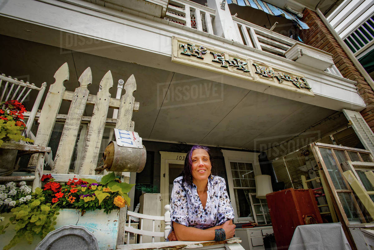 Shabby Chic Shop Portrait Of Female Shop Keeper At Front Porch Shabby Chic Shop Stock Photo