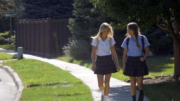 Two Teenage Girls Talking Walking In School Uniforms
