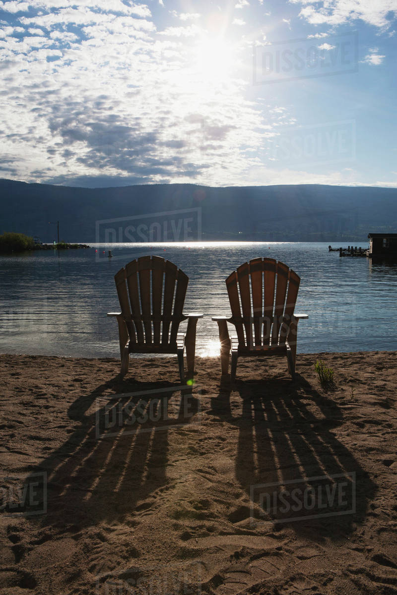 Two Beach Chairs On A Beach With The Sun Burst Out Of The Clouds And Long Shadows Of The Chairs On The Sand Summerland British Columbia Canada Stock Photo Dissolve