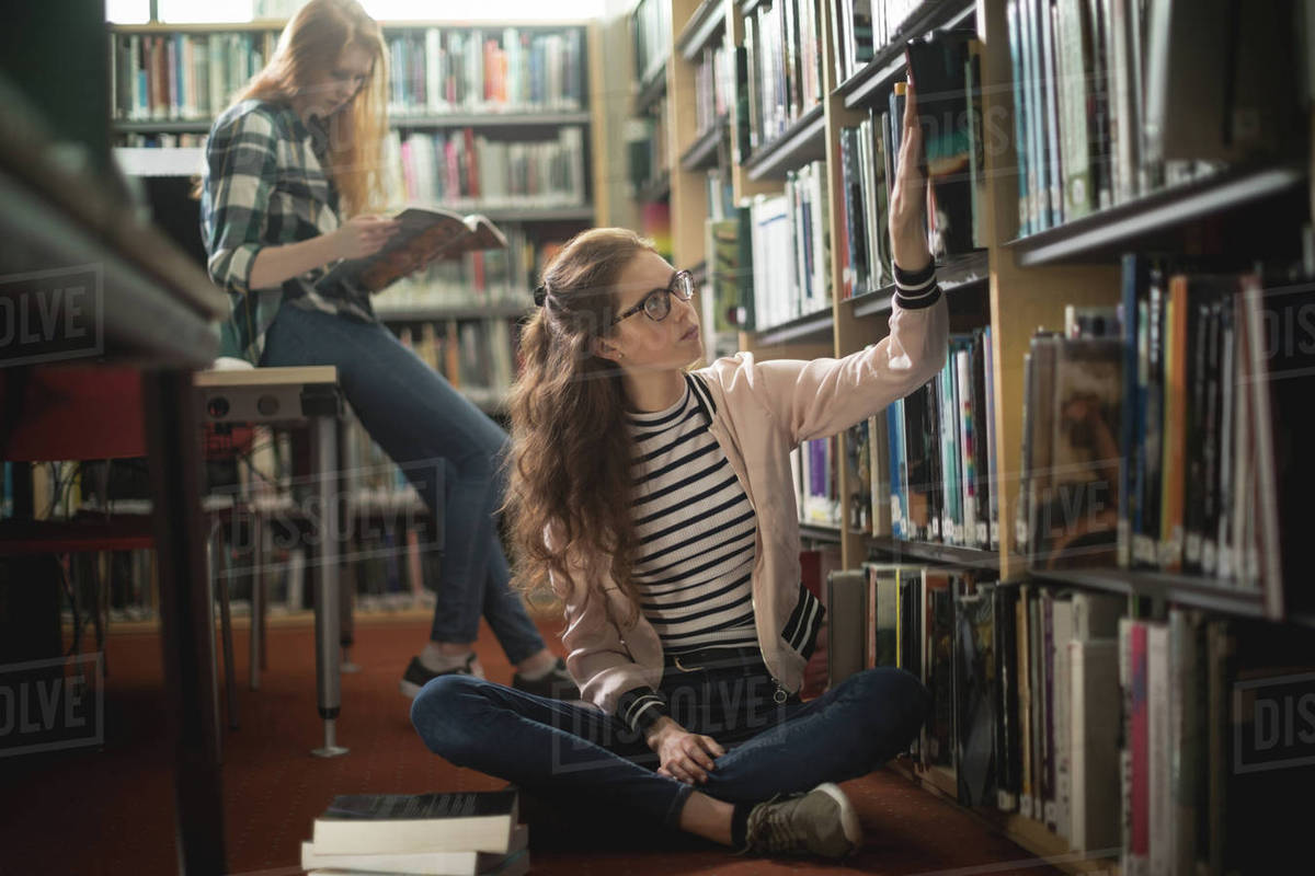 Woman Searching A Book From Shelf In Library Room Stock