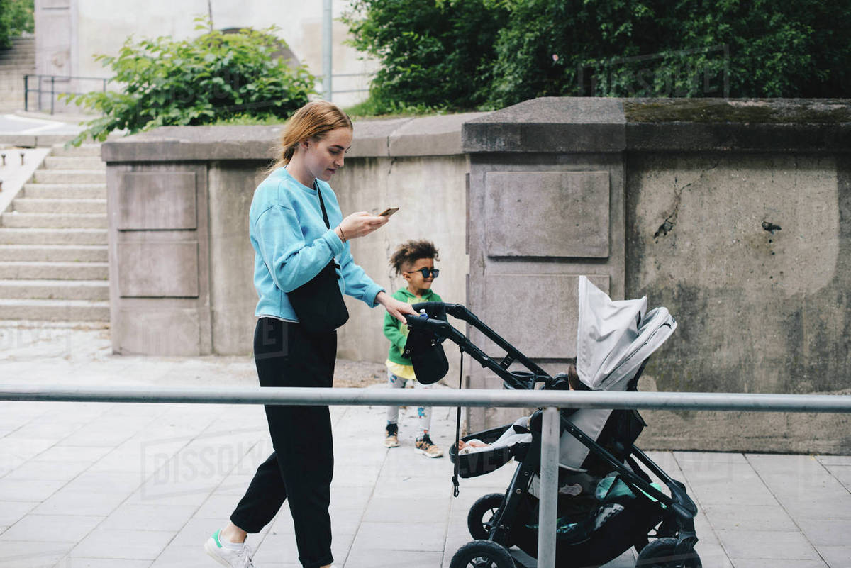 Baby Pushing Pram Youtube Mother With Son Using Mobile Phone While Pushing Baby Stroller On Sidewalk At City Stock Photo