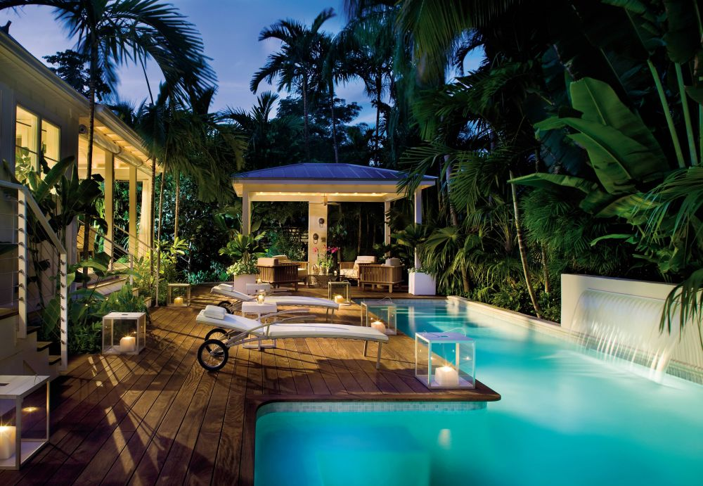 photo of a mid sized tropical green one story exterior in miami - key west style home decor