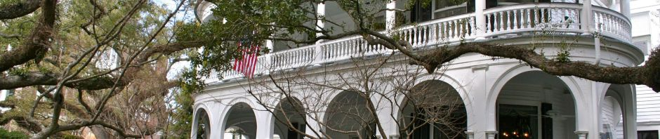 Queen Anne with a Charleston twist. Note the ornate details, arches and shingles
