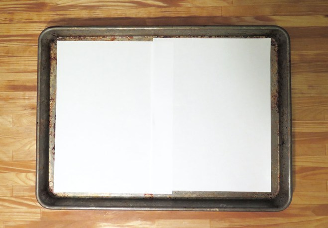 Two pieces of typing paper on a baking sheet.