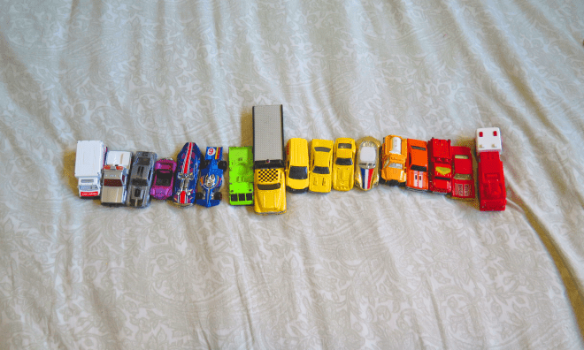 Hot Wheels Matchbox toy cars arranged by color into a rainbow