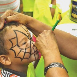 Three year-old Devon Santos was among many children to get his face painted by Dori Stewart at Healthy Hoops.
