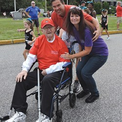 "Retired First Sgt. Charles ""Chubby"" Garman received cheers during the parade, while being chauffered by his son, Chris. Here, Chubby and Chris pose with parade organizer Brookhaven Councilwoman Denise Leslie, herself a Navy veteran."